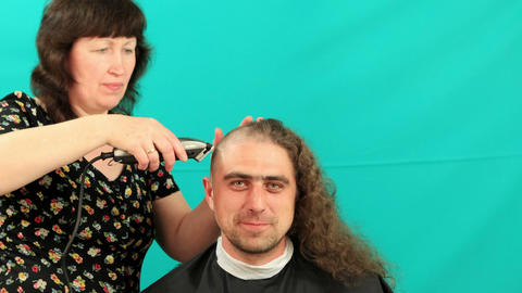Man having an haircut on the green background, timeLapse Stock Video Footage