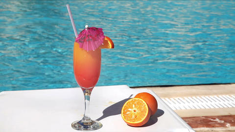 Orange cocktail with umbrella and straw near swimming pool Stock Video Footage