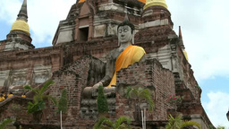 Statue of buddha sits in front of temple ruin in Ayutthaya, Thailand Footage
