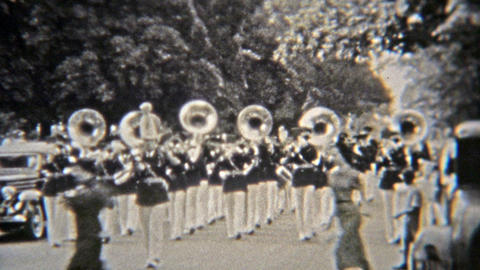 1937: Marching band parading with tuba band horns playing Footage