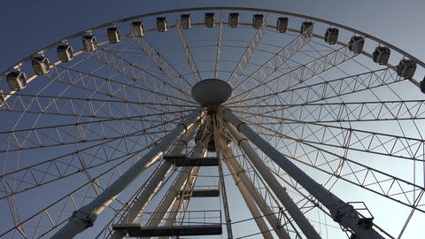 Ferris wheel against the blue sky. 4K Footage