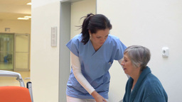 Smiling Nurse Helps Senior Patient In Hospital stock footage