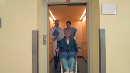 Medical Team With Patient In Wheelchair Walking Out Of Elevator stock footage