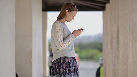 Young pretty girl tourist at the bus stop useing smartphone. Countryside. Europe Footage