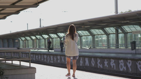 young woman waiting for a train at platform at the station portugal Footage