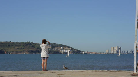Girl takeing picture and looking at the river in portugal belem embankment Footage
