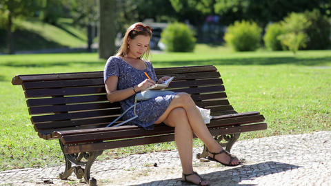 young girl sitting at the bench in a park and making notes Footage