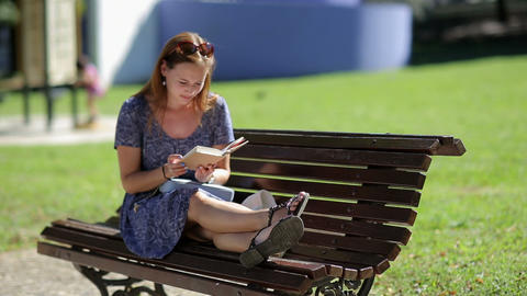 Young woman relaxing, reading a book and sitting on a bench with legs outside in Footage