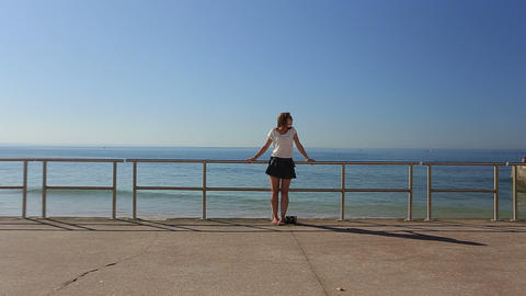 Sunbatheing of a thoughtful beautiful young woman contemplating the sea on a bea Footage