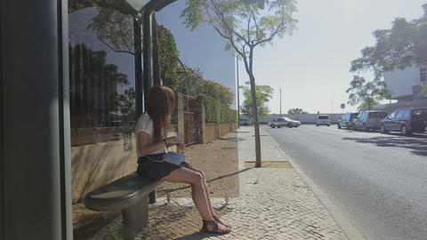 Lonely young girl waiting staying at bus stop in blue skirt and sunglasses, summ Footage