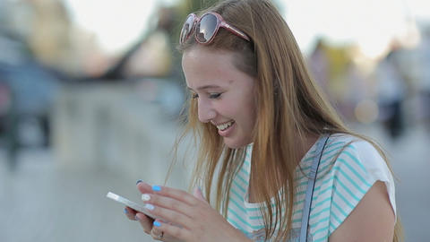 Happy young woman talking smart phone, laugthing in a city embankment sitting in Footage