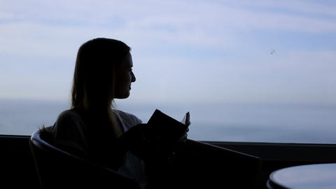 silhouette of young beautiful girl sits in a cafe with panoramic views of atlant Footage