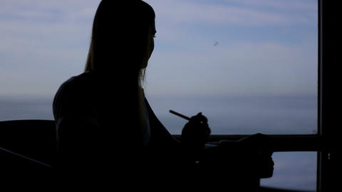 silhouette of young beautiful girl sits in a cafe with panoramic window sea view Footage