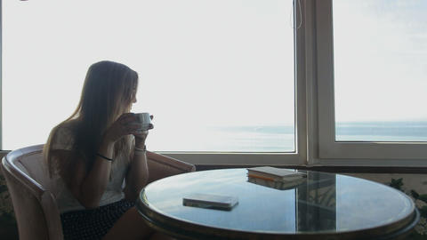 long shot of young beautiful girl sits in a cafe with panoramic views of atlanti Footage
