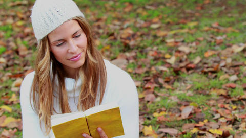 Woman reading a book in park on autumn day Footage