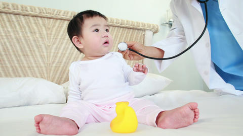 Doctor examining baby on bed Footage