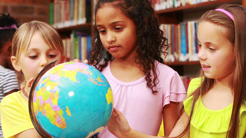 Little girls looking at globe in library Live Action