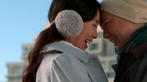 Loving Asian couple in winter clothes hugging each other Footage