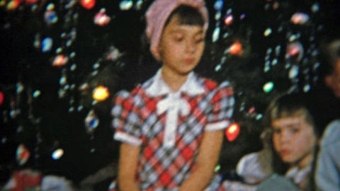 1951: Kids opening Christmas gifts in front of festive tree Footage