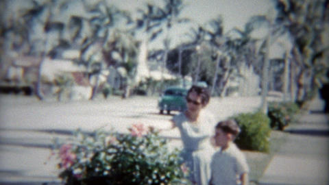1959: Mom and son of tree lined street as old classic car passes Footage