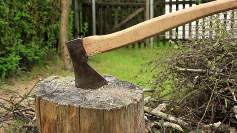 Axe stuck in stump next to firewood pile Footage