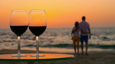 Couple admiring the sunset. In the foreground is the glasses with red wine on th Footage