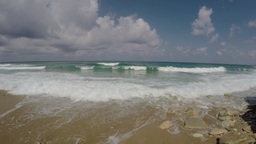 Nice waves rolling to the shore - some surfers in the water, real time in 4K Footage