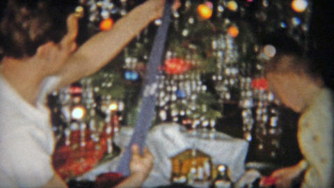 1954: Brother puts Christmas gift formal tie on little brother Footage