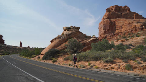 Hitchhiker Walks Along Road in Arches National Park Footage