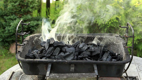 Smoke rising from charcoal placed in grill - wide shot Live Action