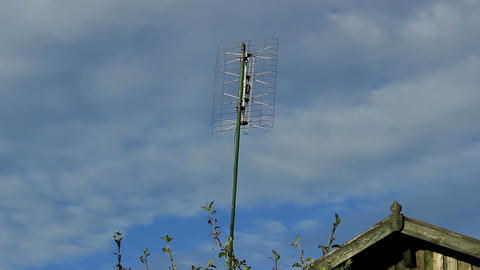 Clouds Above The Roof Of The Cottage And Aerial Antenna On A Sunny, Cloudy Day stock footage