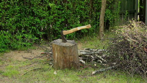 Axe stuck in stump next to firewood - long shot Footage