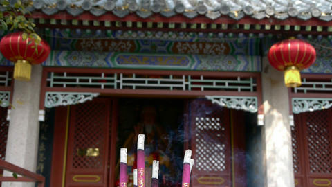 Taoist statues Buddha in door,Burning incense in Incense burner,red lantern,Wind Footage