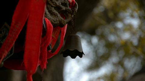 Dragon and metal bell on censer,Red ribbon blowing in wind,Trees,shade Footage