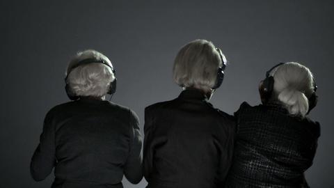 Senior women wearing headphones and swaying to music Stock Video Footage