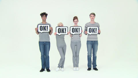Time lapse of four people with signs that say ok Live Action