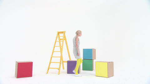Young woman stacking coloured boxes and using stepladder Stock Video Footage