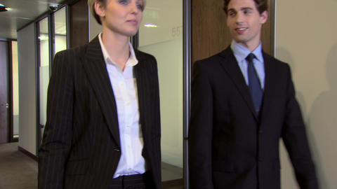 Businessman and businesswoman walking and talking Stock Video Footage