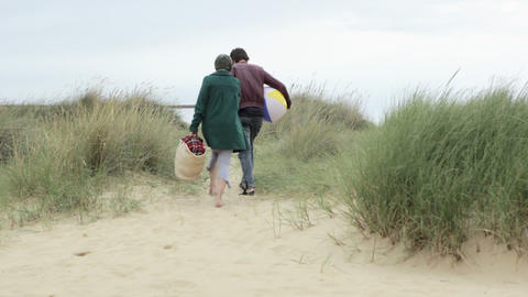 Young couple walking over sand dune Footage