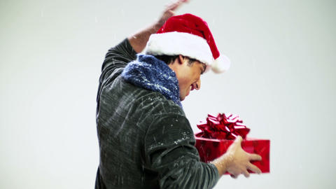 Young man with santa hat and gift dancing in snow fall Stock Video Footage