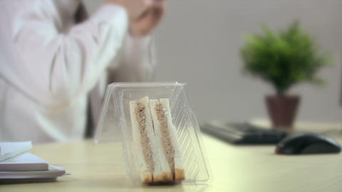 Office worker eating sandwich Stock Video Footage