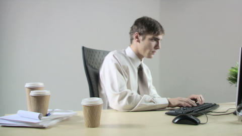 Office worker at desk knocking coffee cup over Stock Video Footage