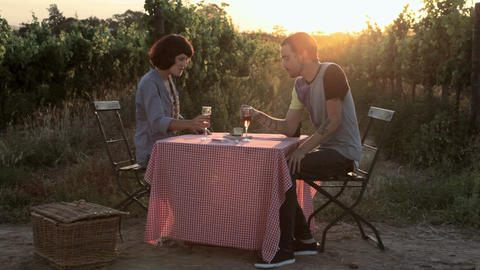 Young couple at table in field, having wine and kissing Stock Video Footage