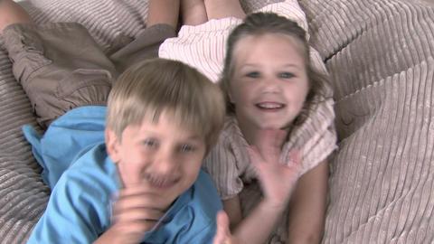 Girl and boy jumping onto beanbag and waving at camera Stock Video Footage