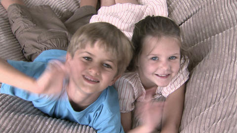 Girl and boy jumping onto beanbag and waving at camera Stock Video Footage
