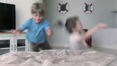 Boy and girl running and jumping onto beanbag Stock Video Footage