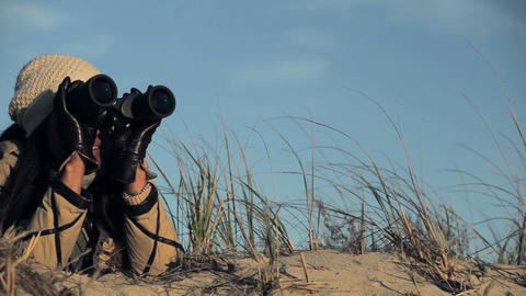 Woman on beach using binoculars Stock Video Footage