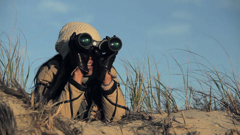 Woman on beach using binoculars Stock Video Footage