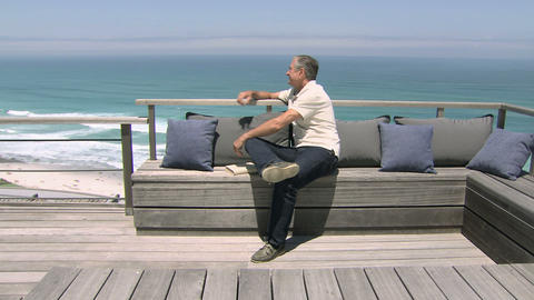 Man relaxing by the sea, looking at view and reading book Stock Video Footage