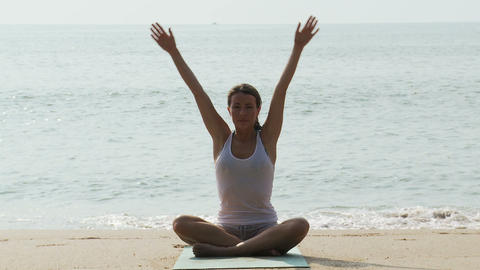 Woman practicing yoga by the sea Stock Video Footage